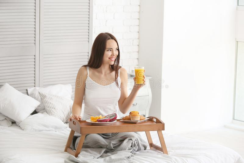 Beautiful young woman having breakfast on bed at home royalty free stock image
