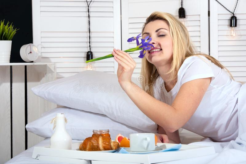 Beautiful young woman having breakfast in bed. Surprise from beloved husband. Celebrating a woman`s day, mother`s day. Celebrating a woman`s day, mother`s day royalty free stock photos