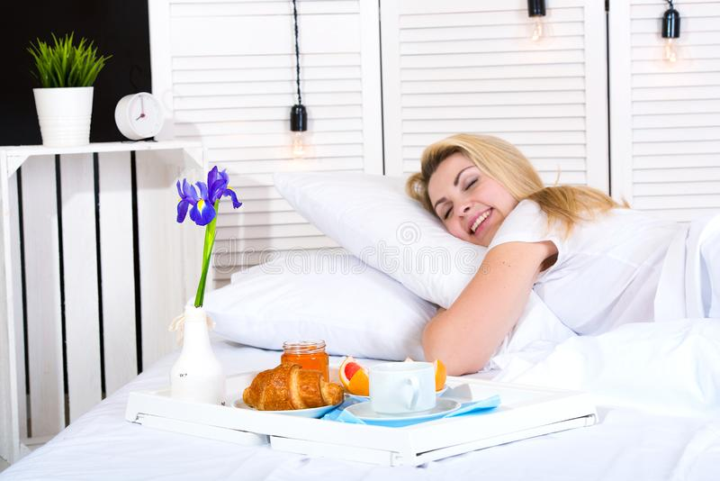 Beautiful young woman having breakfast in bed. Surprise from beloved husband. Celebrating a woman`s day, mother`s day. Celebrating a woman`s day, mother`s day royalty free stock images