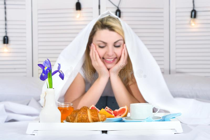 Beautiful young woman having breakfast in bed. Surprise from beloved husband. Celebrating a woman`s day, mother`s day. Celebrating a woman`s day, mother`s day royalty free stock photography
