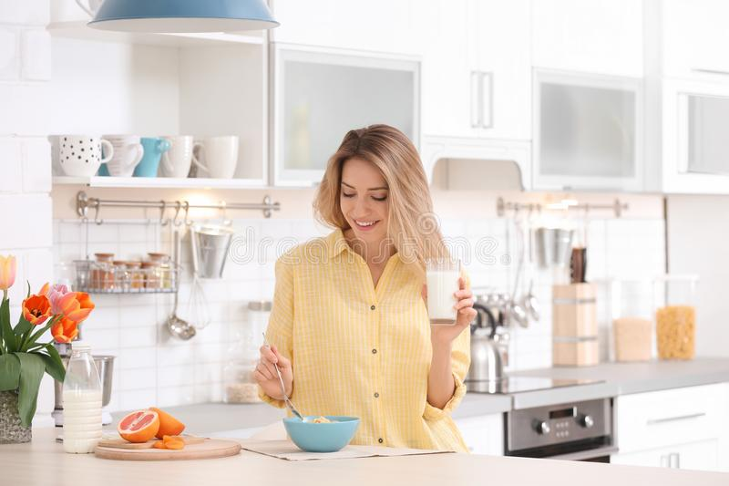 Beautiful young woman having breakfast in kitchen stock photo