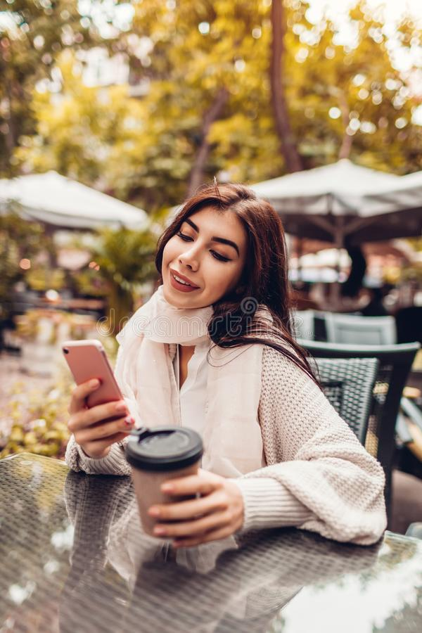 Beautiful young woman having coffee in outdoor cafe while using smartphone. Portrait of stylish girl typing message stock images