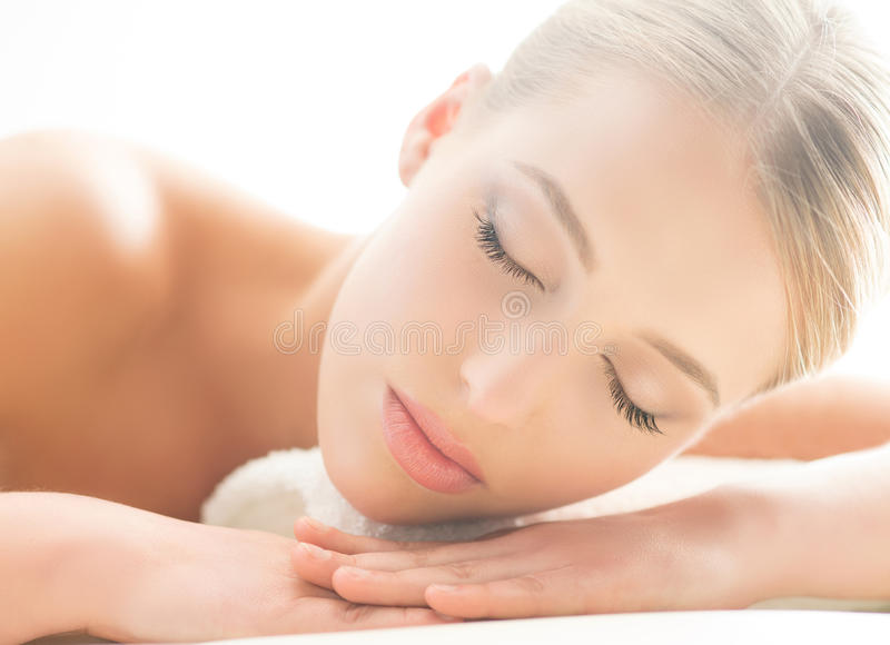 Beautiful young woman having leisure lying in a mat in spa.  stock images