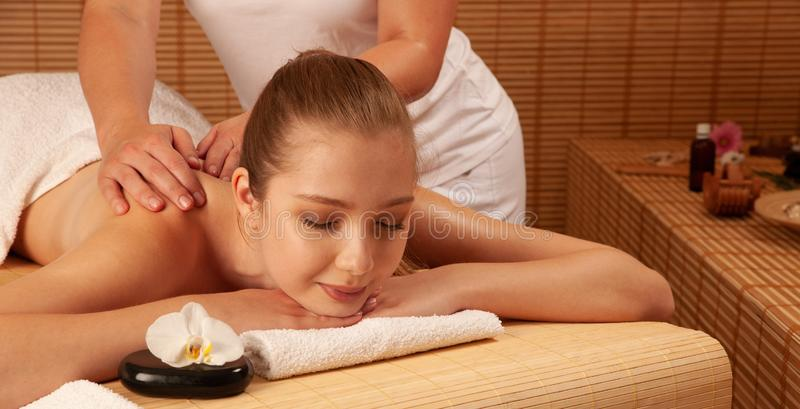 Beautiful young woman having a massage treatment in spa salon - wellness royalty free stock photo