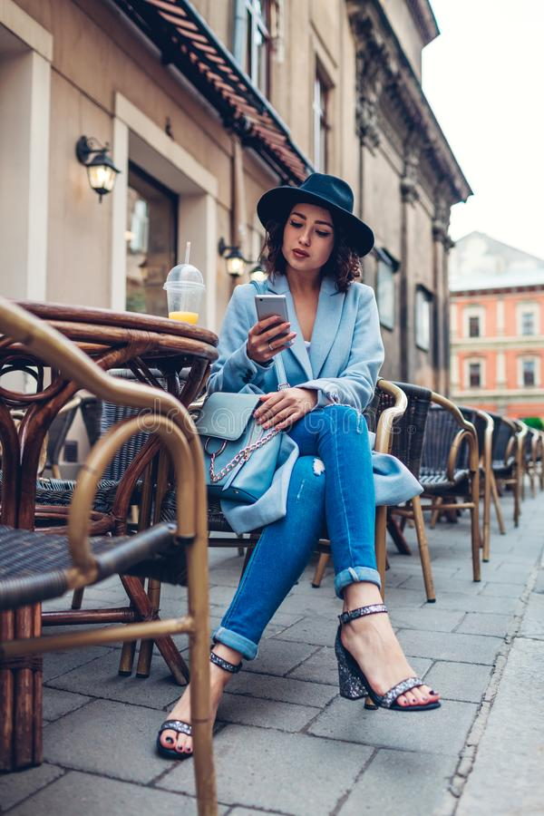Beautiful young woman having orange juice in outdoor cafe while using smartphone royalty free stock photo