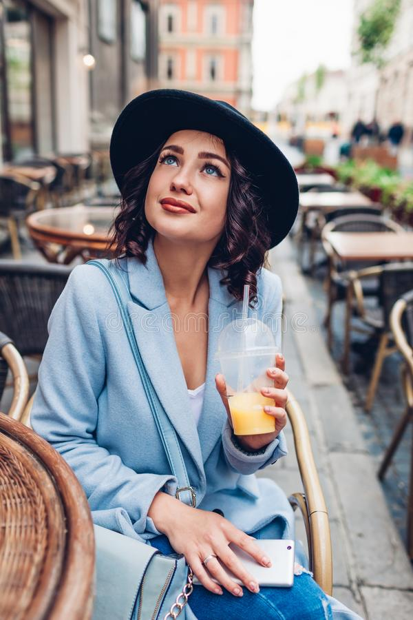 Beautiful young woman having orange juice in outdoor cafe while using smartphone royalty free stock photography