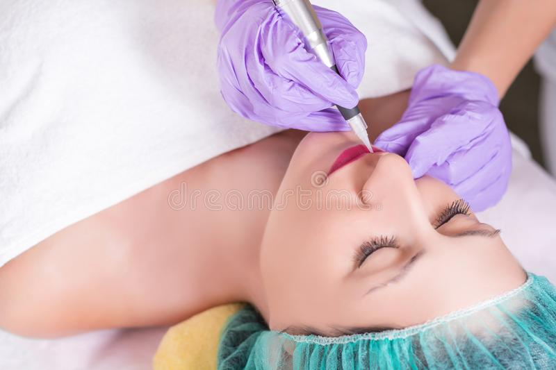 Woman having permanent make up on lips in professional beauty studio stock photo