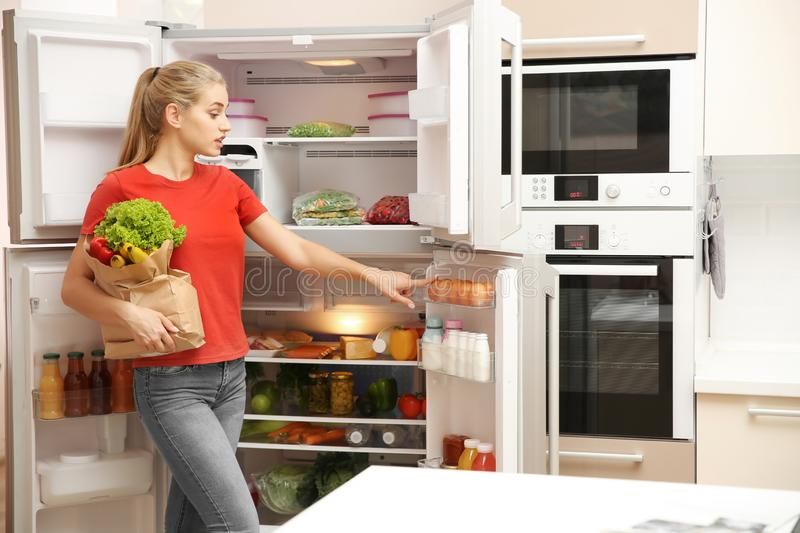 Beautiful young woman with healthy food. In paper bag near refrigerator at home stock photography