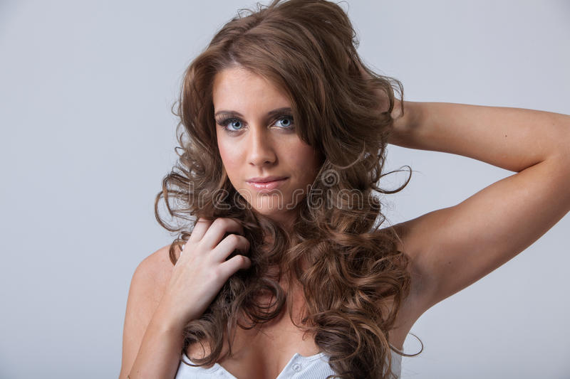 Beautiful young woman with healthy long curly hair stock photography