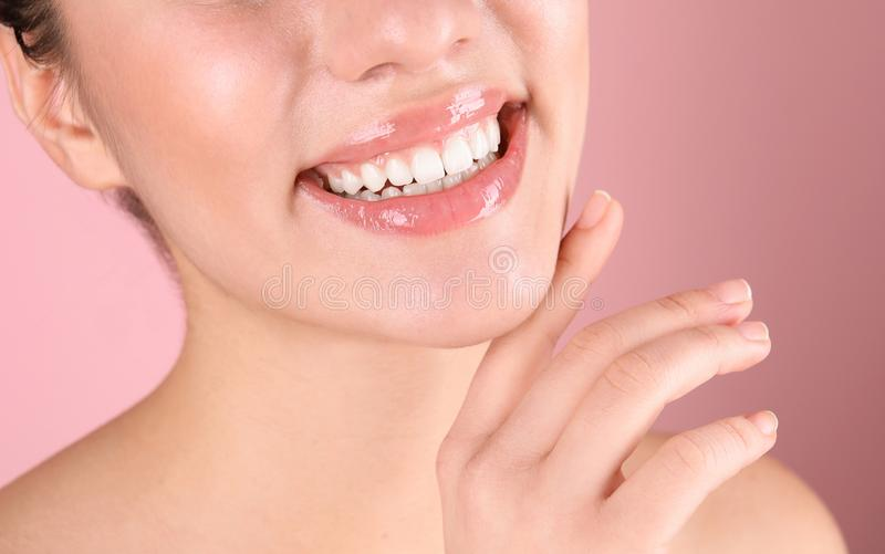 Beautiful young woman with healthy teeth on color background. Closeup stock photo