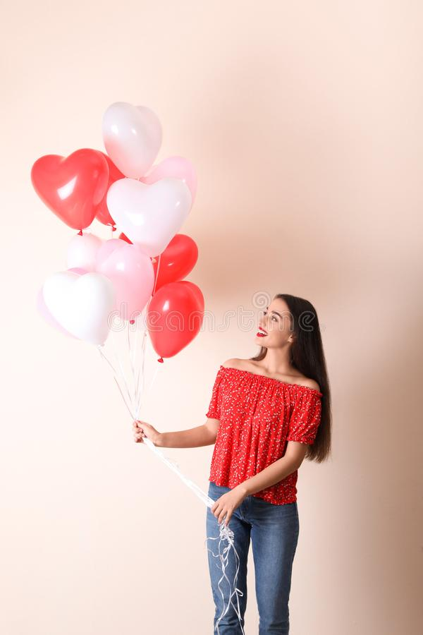 Beautiful young woman with heart shaped balloons on background. Valentine`s day celebration stock images