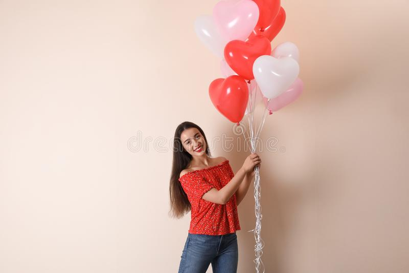 Beautiful young woman with heart shaped balloons on background. Valentine`s day celebration stock image
