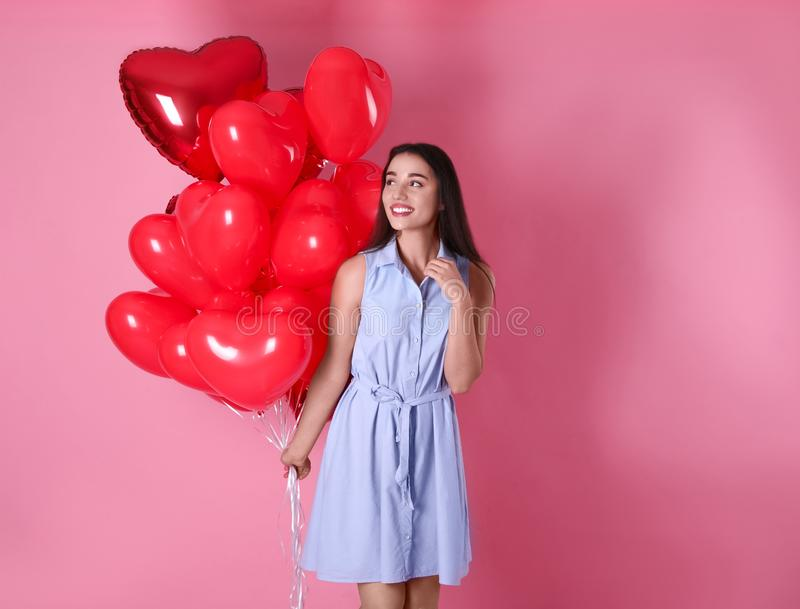 Beautiful young woman with heart shaped balloons on background. Valentine`s day celebration royalty free stock images