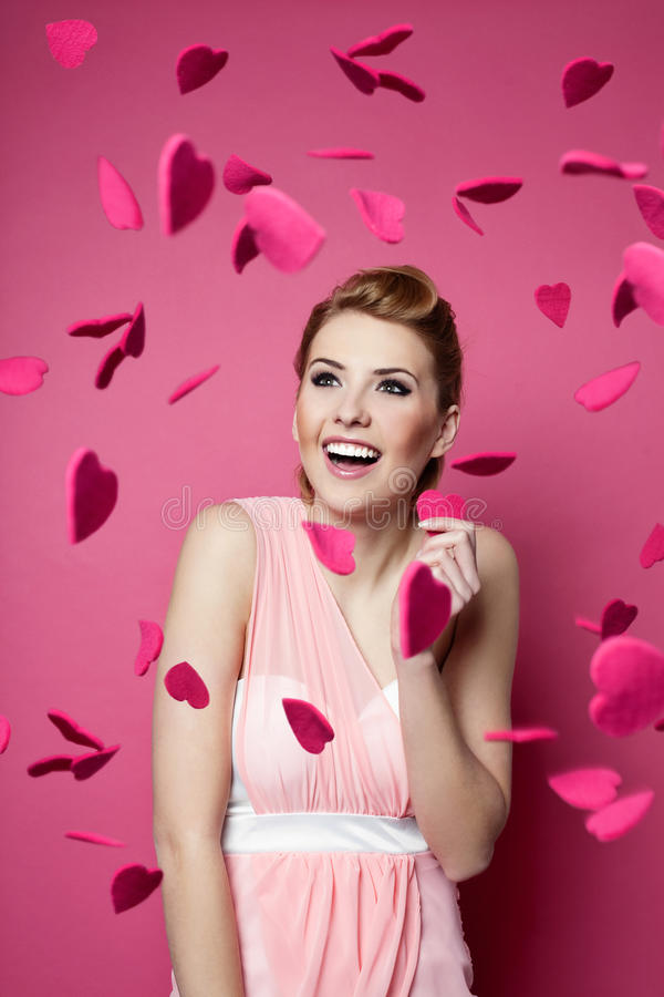 Beautiful young woman with hearts falling around. Valentine's day. Beautiful young woman with hearts falling around her royalty free stock images