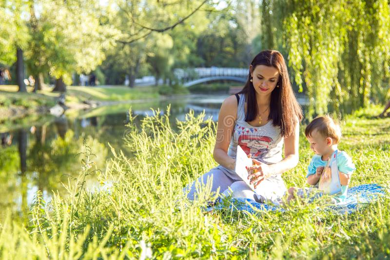 Beautiful young woman and her adorable little son play in sunny park, read books royalty free stock photo