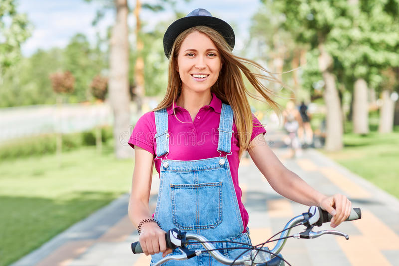Beautiful young woman with her bicycle at the park stock photos