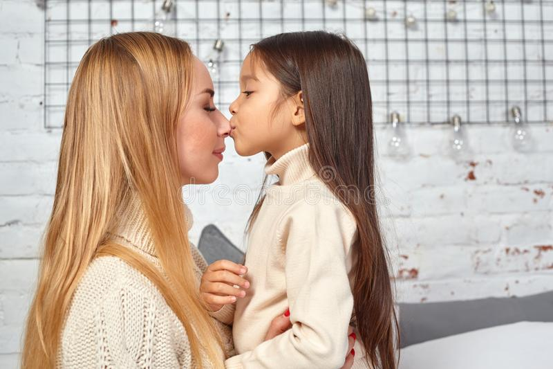 Beautiful young woman and her charming little daughter are hugging. stock photography