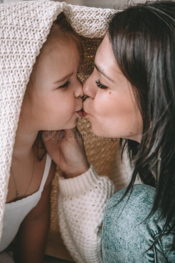 Beautiful young woman with her daughter showing love and affection stock photos