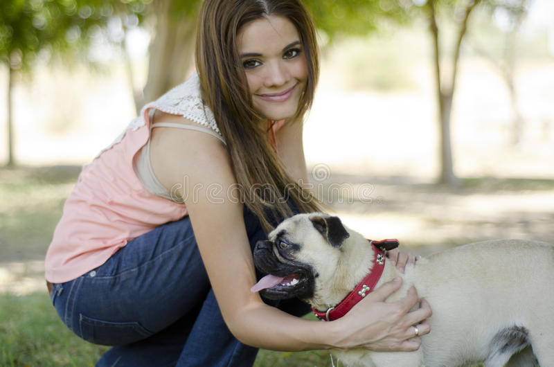 Beautiful young woman and her dog. Young beautiful woman playing and spending some time with her dog in a park royalty free stock photography