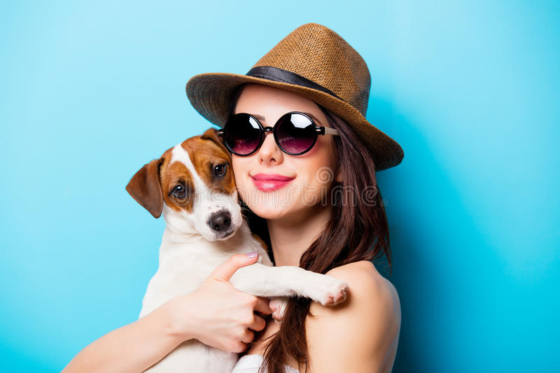 Beautiful young woman with her dog standing in front of wonderful blue background stock photos