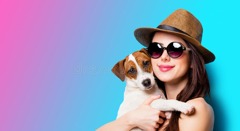 Beautiful young woman with her dog standing in front of wonderful blue background royalty free stock photo
