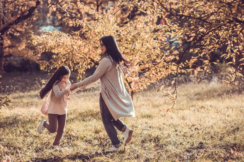 Beautiful young woman and her kid in autumn garden royalty free stock photography