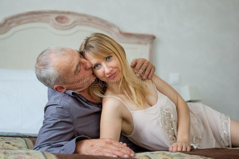 Beautiful Young Woman with Her Senior Lover Lying on the Bed. Man Kissing His Girlfriend. Portrait of Happy Lovely Couple royalty free stock photography