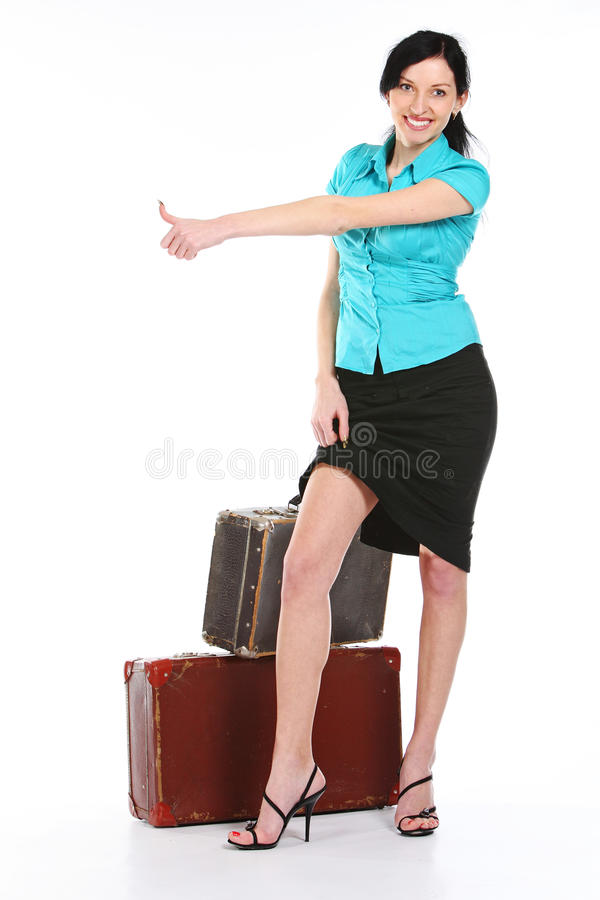 Beautiful young woman hitch hiking. With old leather suitcase, isolated on white royalty free stock photography