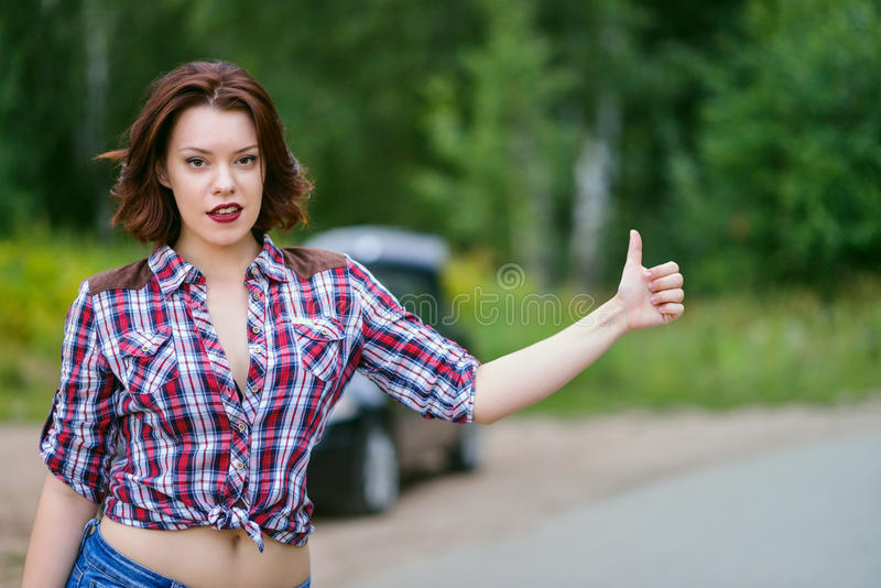 Beautiful young woman hitchhiking gesture at countryside, broken car on background. Beautiful young woman hitchhiking gesture at countryside, broken car at royalty free stock images