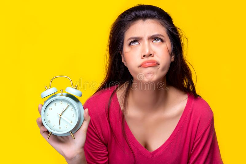 Beautiful young woman hold alarm clock and gets lazy, boring, when she has to wake up early for work on Monday morning. Pretty stock photos