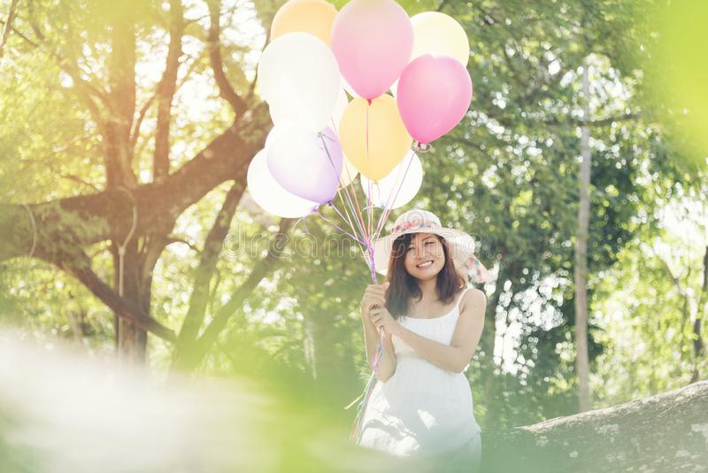 Beautiful young woman holding air balloons in garden royalty free stock images