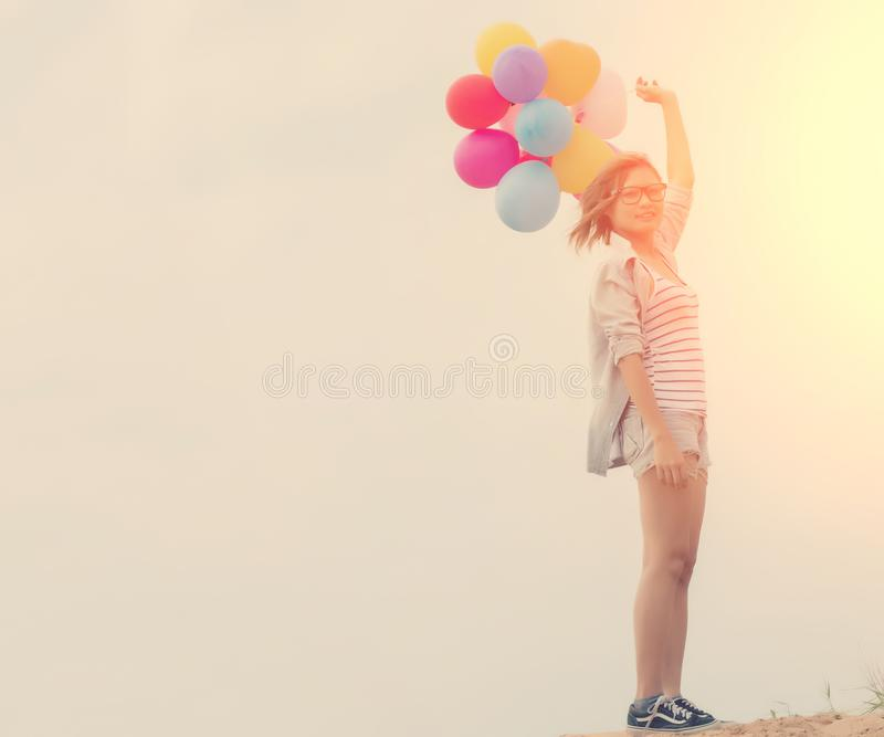 Beautiful young woman holding balloon standing on the sand look royalty free stock images