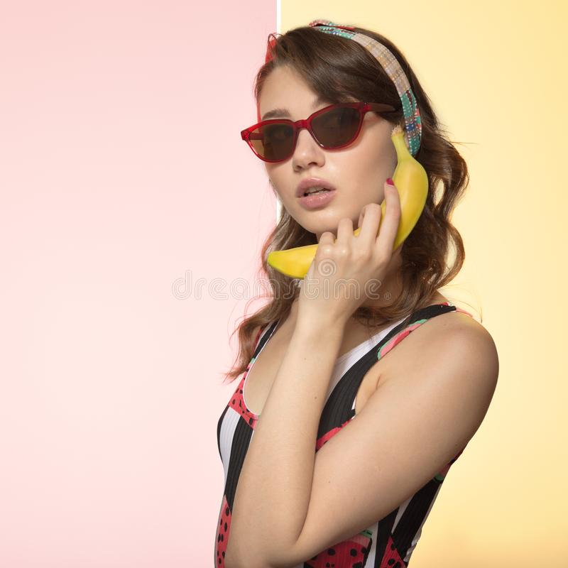 Beautiful young woman holding a banana near the ear. Woman in glasses on a colored background. Pop Art. Beautiful young woman holding a banana near the ear stock photos