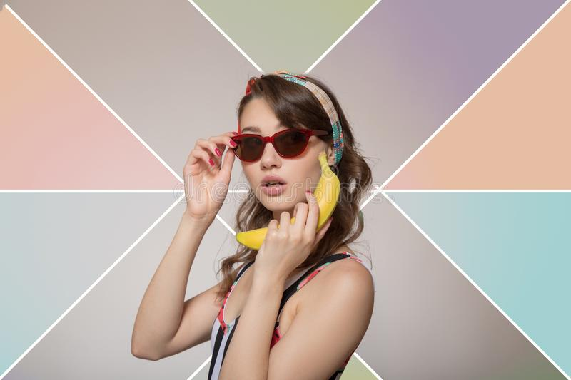 Beautiful young woman holding a banana near the ear. Woman in glasses on a colored background. Pop Art. Beautiful young woman holding a banana near the ear stock photo