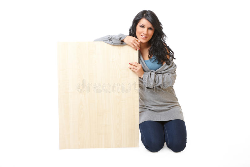Beautiful young woman holding a blank wooden board stock image