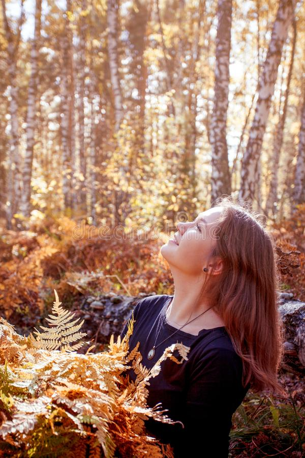 Beautiful young woman holding a bunch of autumn leaves, romantic dreaming mood, fall walking, relax time in the forest stock photo