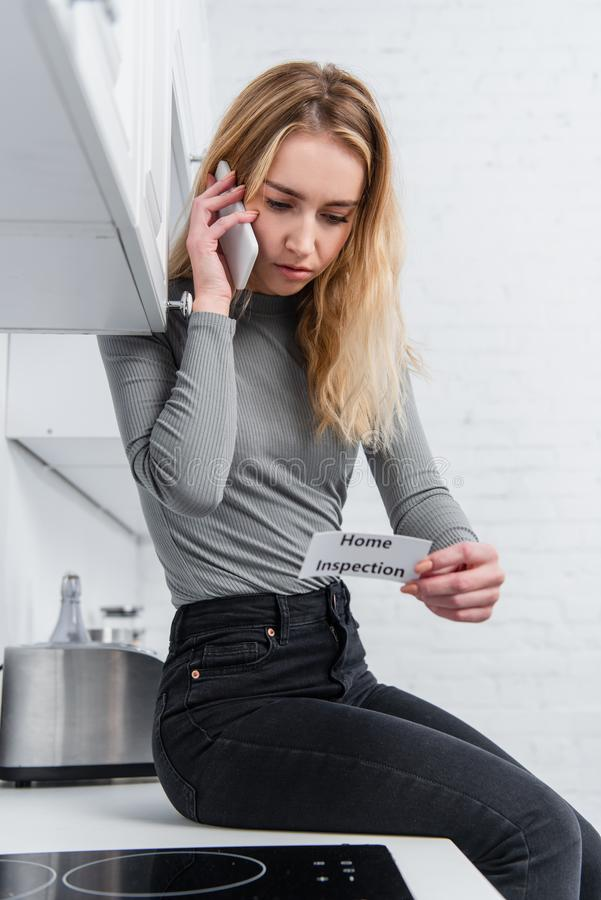 Beautiful young woman holding card with lettering home inspection and talking on smartphone. In kitchen royalty free stock photos