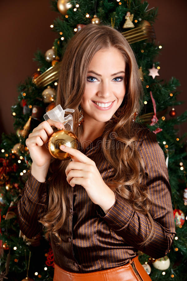 Beautiful young woman holding a Christmas tree orn royalty free stock image