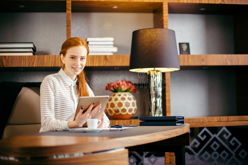 Beautiful young woman holding digital tablet and looking at camera with smile. Beautiful redhead young woman holding digital tablet and looking at camera with royalty free stock images
