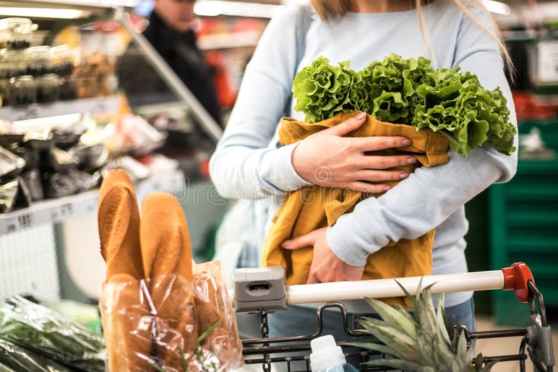 Young woman holding eco bag with greenery. Beautiful young woman holding eco bag with greenery in grocery store. Healthy food shopping concept stock photos