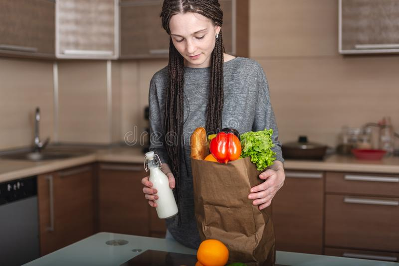 Young woman holding full paper bag with products in hands on the background of the kitchen. Fresh organic food stock photography