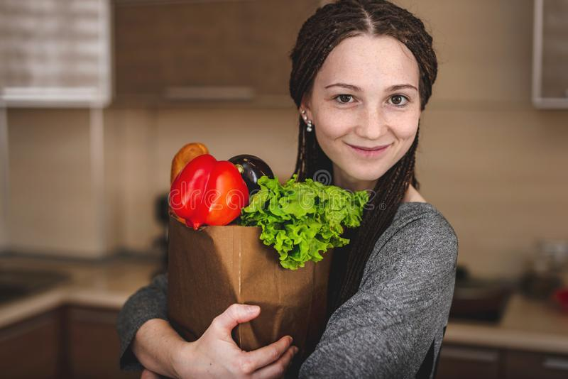 Woman holding full paper bag with products in hands on the background of the kitchen. Healthy and fresh organic food stock image