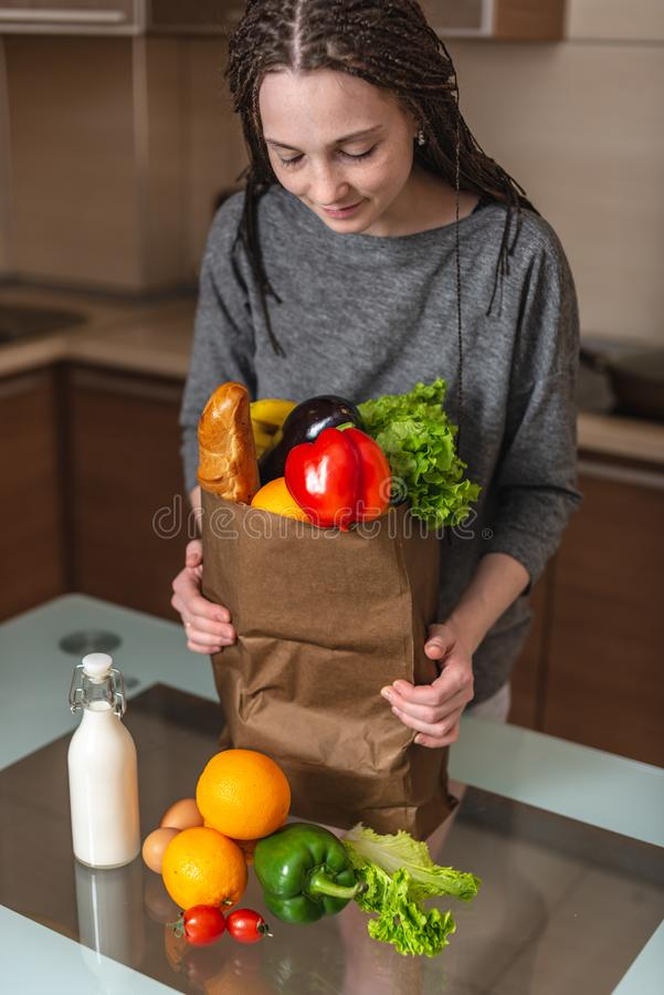 Woman holding full paper bag with products in hands on the background of the kitchen. Healthy and fresh organic food royalty free stock photos
