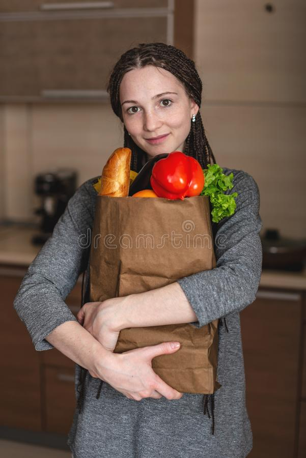 Woman holding full paper bag with products in hands on the background of the kitchen. Healthy and fresh organic food royalty free stock photography