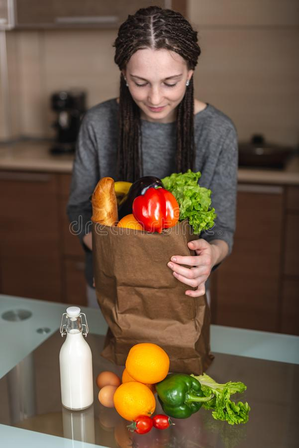 Woman holding full paper bag with products in hands on the background of the kitchen. Healthy and fresh organic food royalty free stock photo