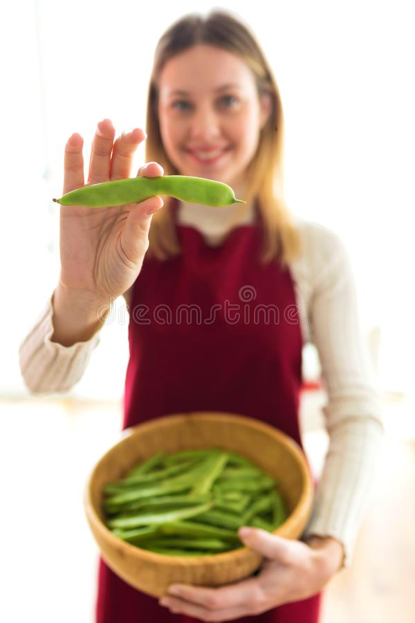 Beautiful young woman holding green beans in round wooden bowl white royalty free stock images
