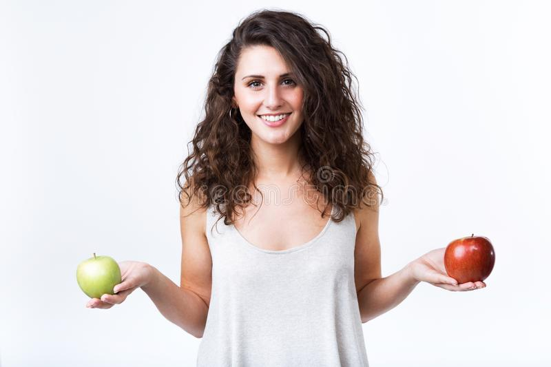 Beautiful young woman holding green and red apples over white background. stock photos