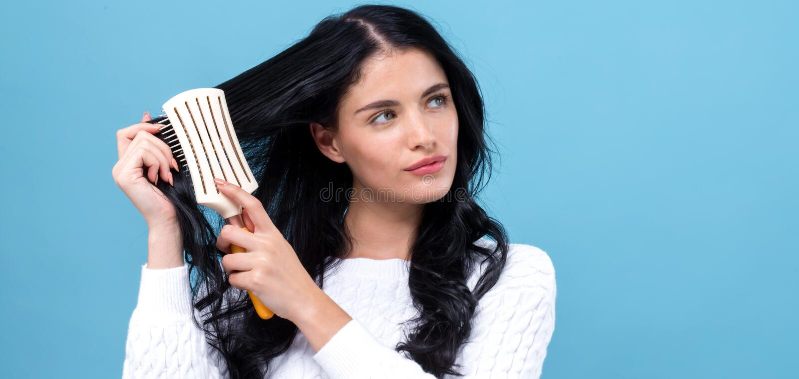 Beautiful young woman holding a hairbrush royalty free stock photos