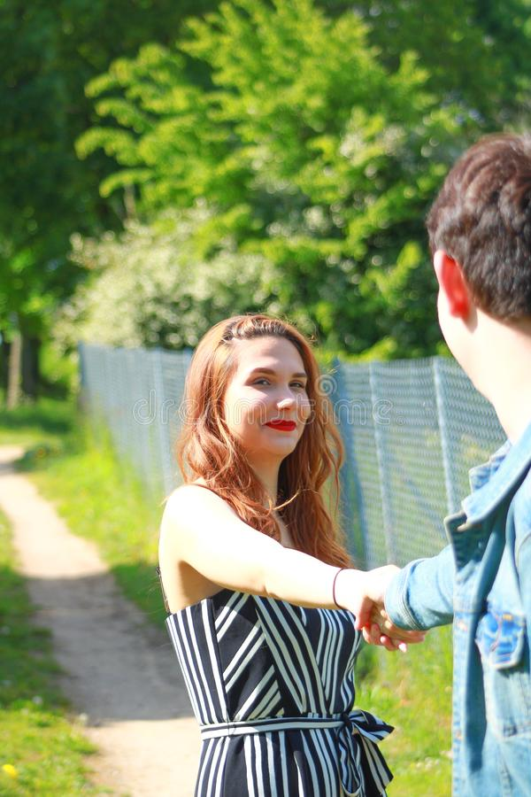 Beautiful young woman holding the hand of a boy in the countryside royalty free stock photography