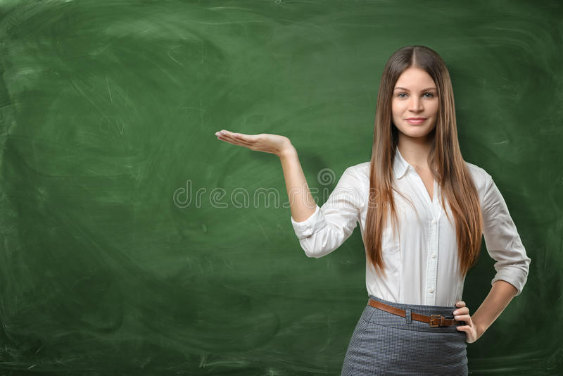 Beautiful young woman holding her open palm and showing at the empty area on the green chalkboard behind her. Advertising product. Business development. Having royalty free stock photo